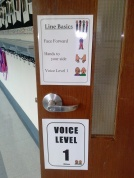 Special signs hang on our door to remind us of what to do in the line.