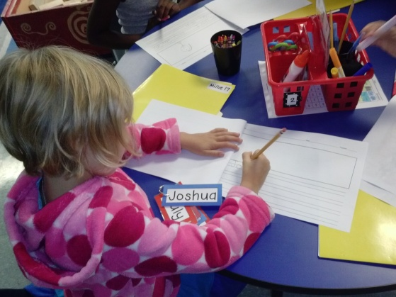 Millie shows off her word wall skills as she writes Joshua's name.  There are rings with the word wall words that hang under the regular words that kiddos can take to their tables to use and return.
