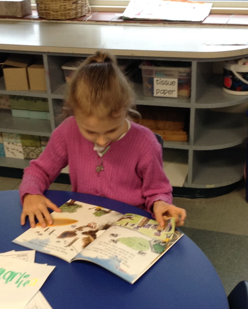 Ella Marie reads quietly at her table to start the day.