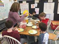 Mrs. Raeber shares popcorn at the kitchen table.