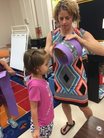 Ms. Turken helps Alice tape her creation together.